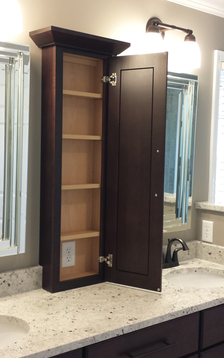 tall narrow storage cabinet containing a handy outlet keeps clutter