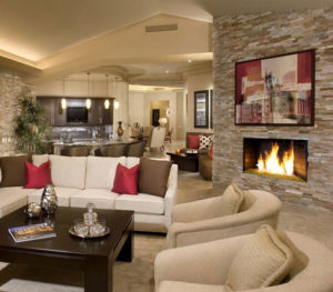A large fireplace, warm colors, and carpeting throughout make this open area cozy and inviting.
